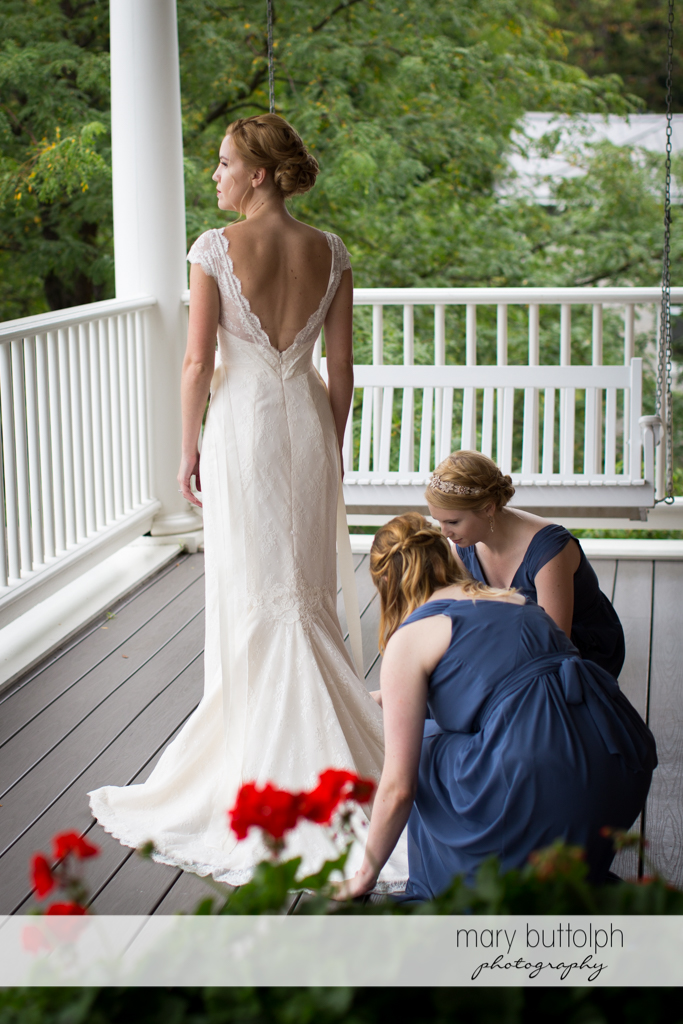 Bride stands on the porch as bridesmaids fix her wedding dress at the Inns of Aurora Wedding