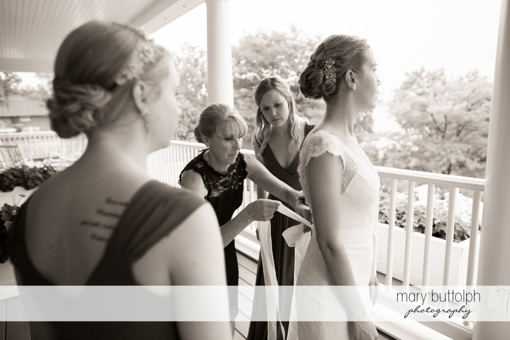 Bride's mother ties her daughter's wedding gown at the Inns of Aurora Wedding