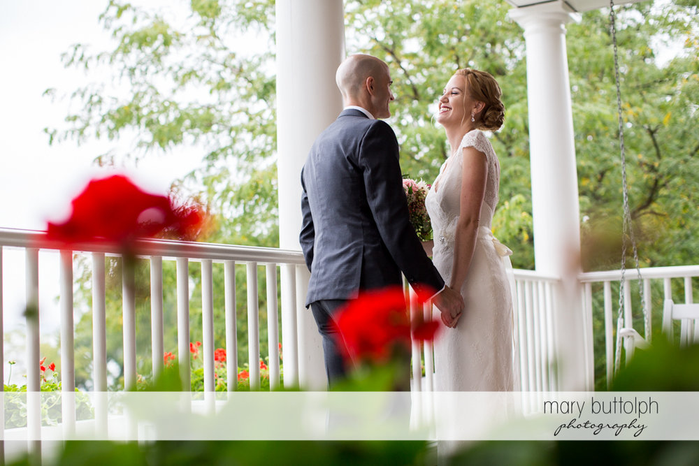 Couple hold hands on the porch at the Inns of Aurora Wedding