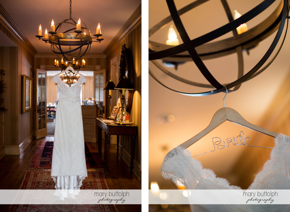 Bride's personalized hanger and wedding dress hang from the chandelier at the Inns of Aurora Wedding