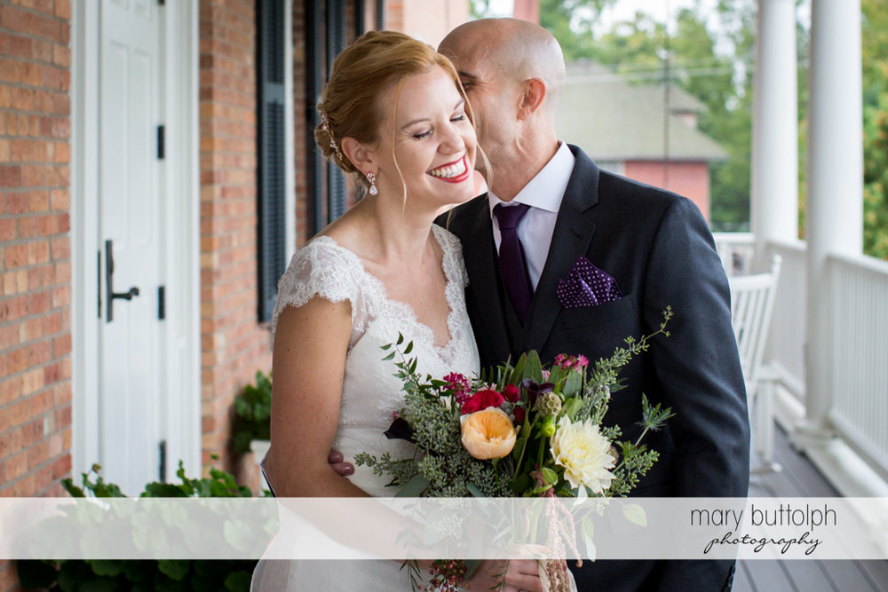 Groom whispers to the bride on the porch at the Inns of Aurora Wedding