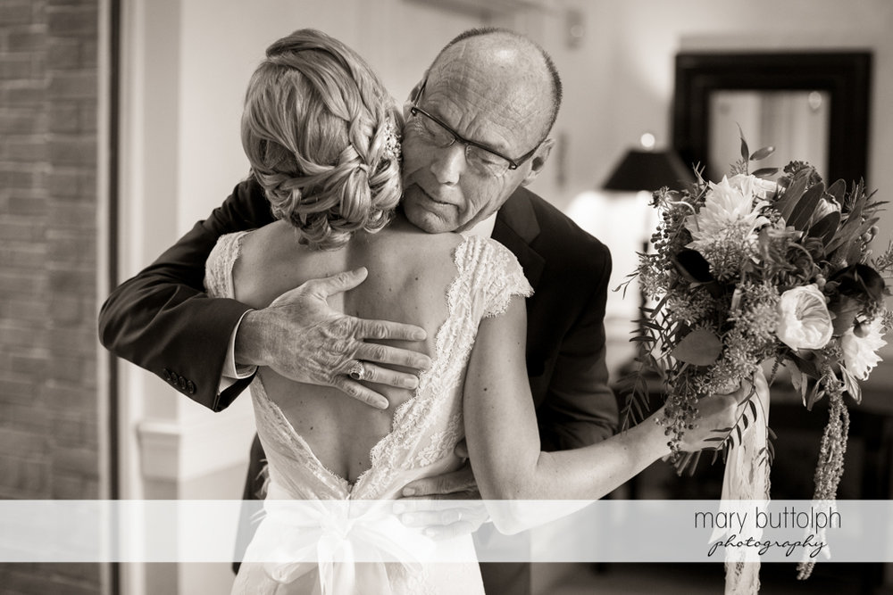 Bride embraces her father on the porch at the Inns of Aurora Wedding
