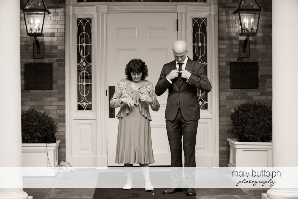 Groom and guest fix their clothes in front of a door at the Inns of Aurora Wedding
