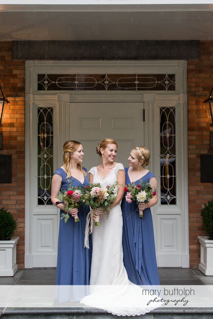 Bride and bridesmaids pose in front of a door at the Inns of Aurora Wedding