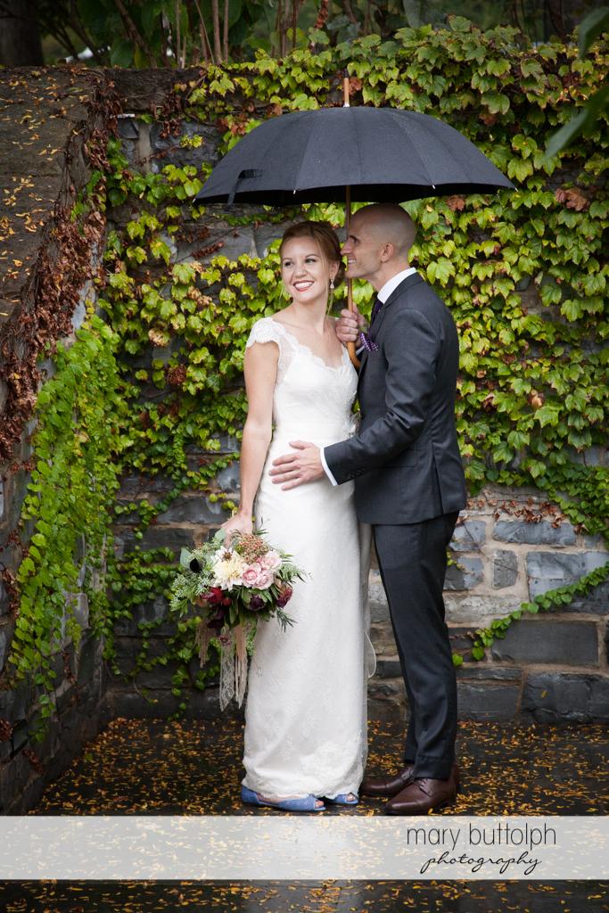 Couple share an umbrella near a brick wall at the Inns of Aurora Wedding