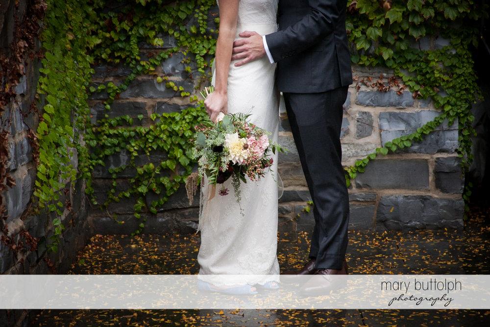 Medium shot of couple standing near a brick wall at the Inns of Aurora Wedding