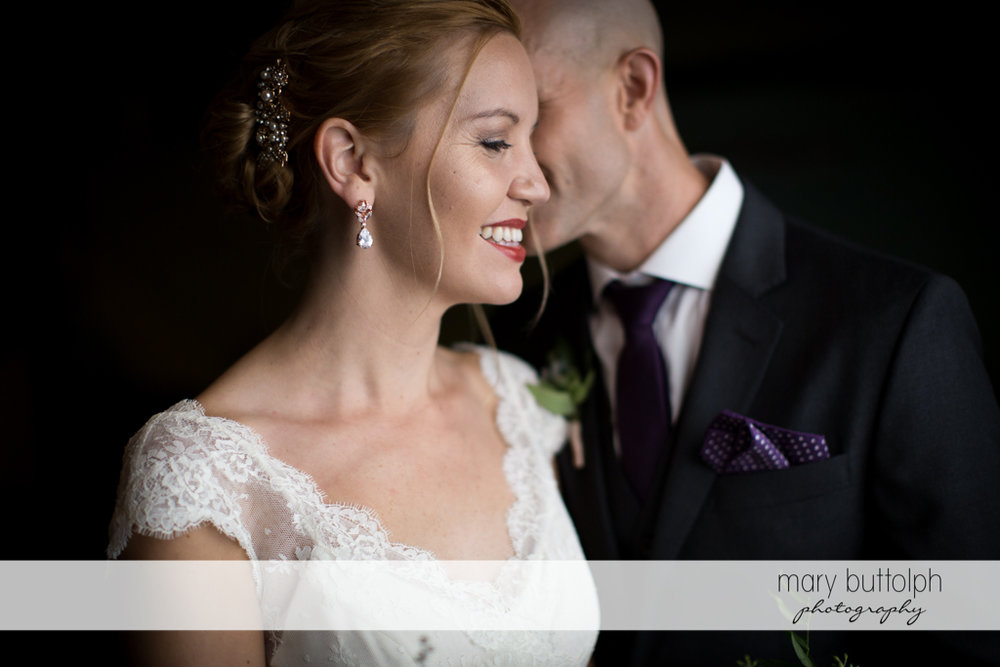 Bride smiles as the groom whispers to her at the Inns of Aurora Wedding