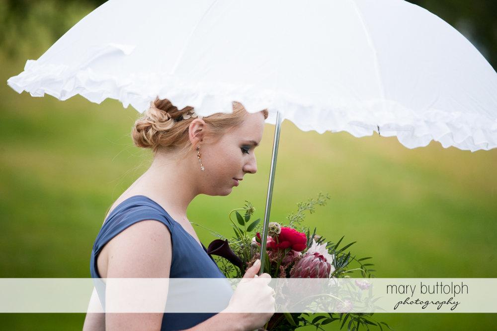 Bridesmaid carries an umbrella at the Inns of Aurora Wedding