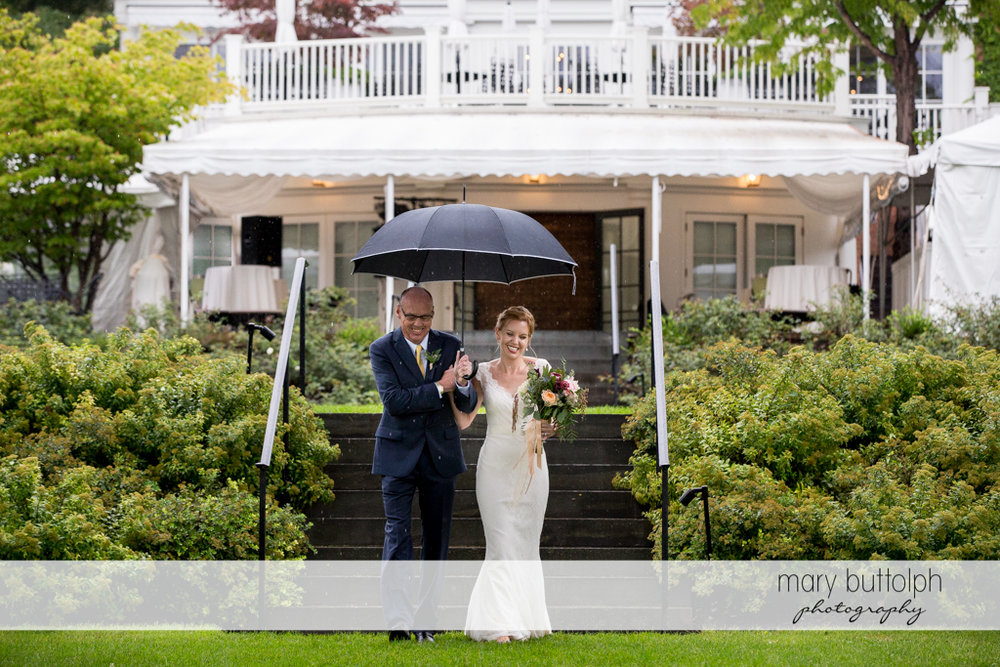 Bride's father shields his daughter from the rain at the Inns of Aurora Wedding