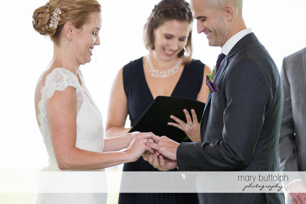 Groom puts the wedding ring on the bride's finger at the Inns of Aurora Wedding