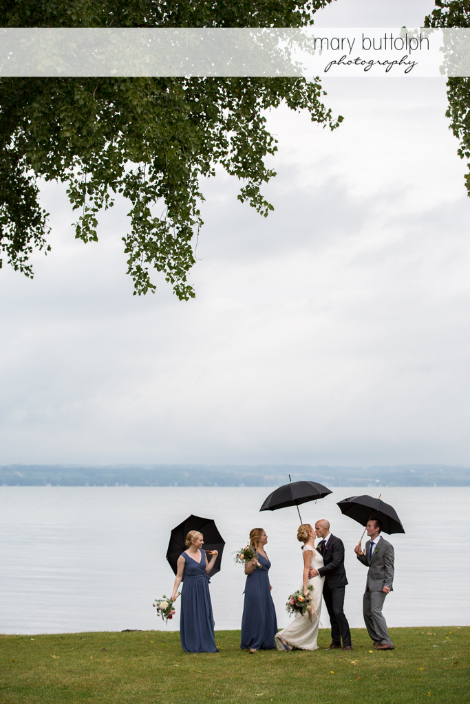 The wedding party with umbrellas pose near the lake at the Inns of Aurora Wedding