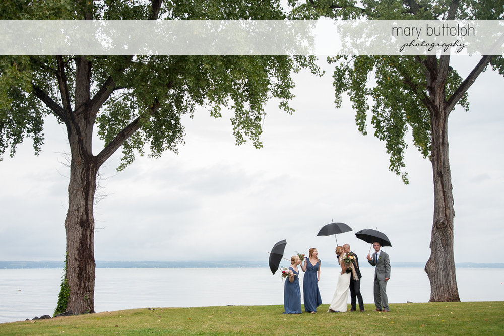 Long shot of the wedding party with umbrellas by the lake at the Inns of Aurora Wedding