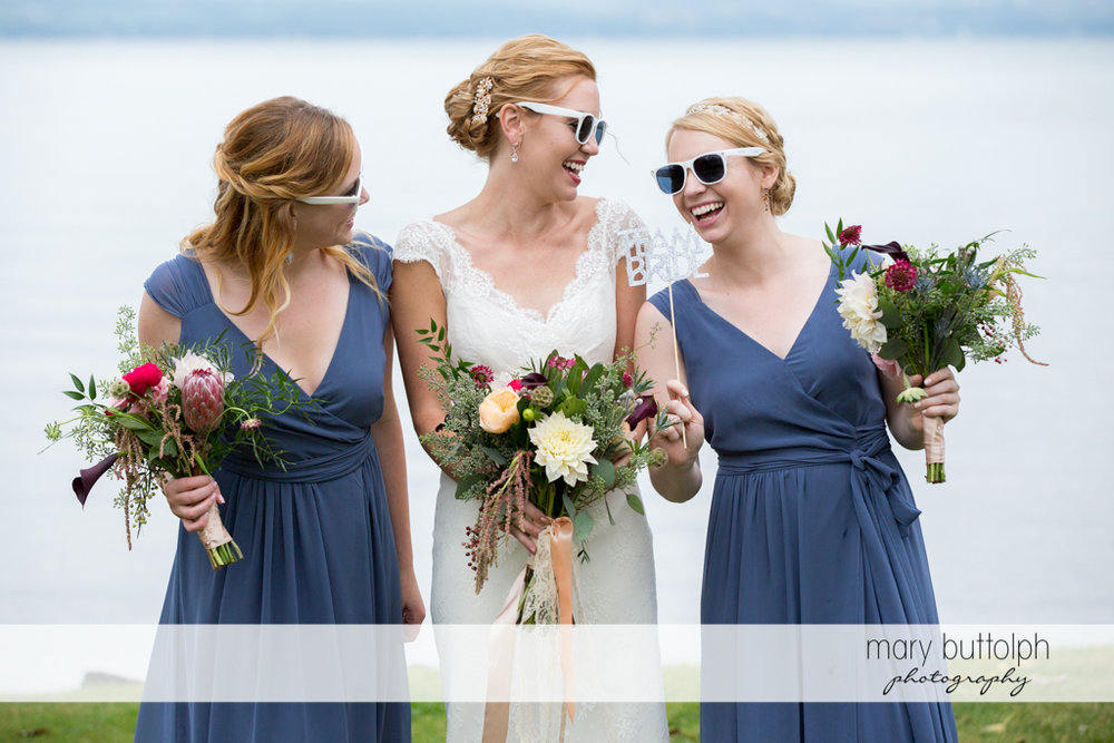 Bride and bridesmaids wear sunglasses in front of the lake at the Inns of Aurora Wedding