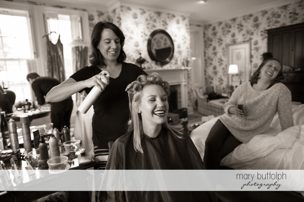 Bride and her friends laugh while her hair is being fixed at the Inns of Aurora Wedding