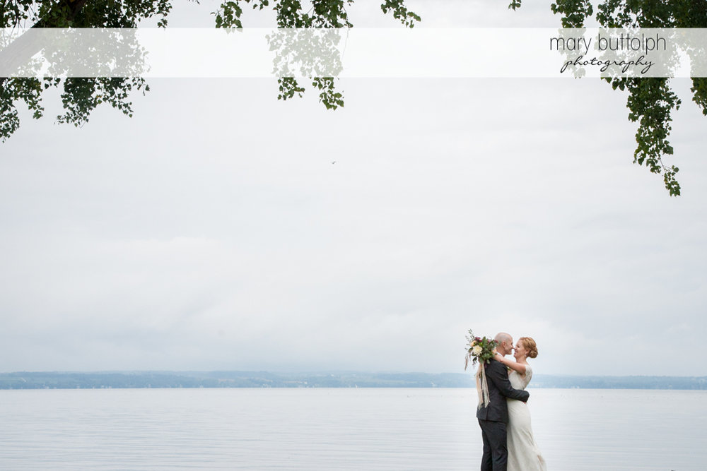 Couple embrace by the lake at the inns of Aurora Wedding