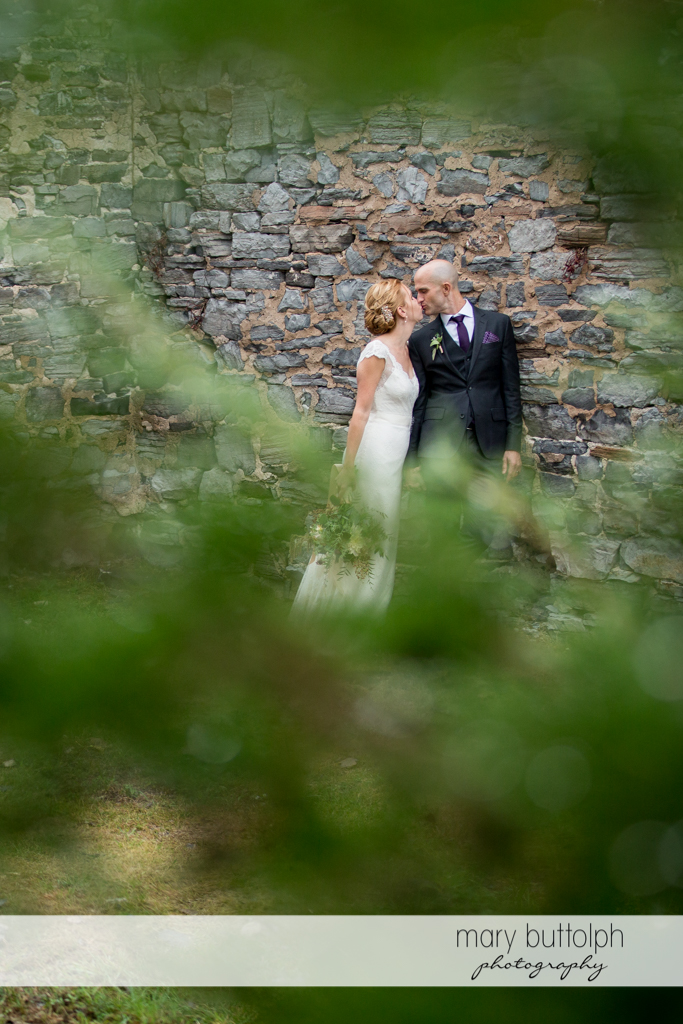 Couple kiss in front of a stone wall at the Inns of Aurora Wedding