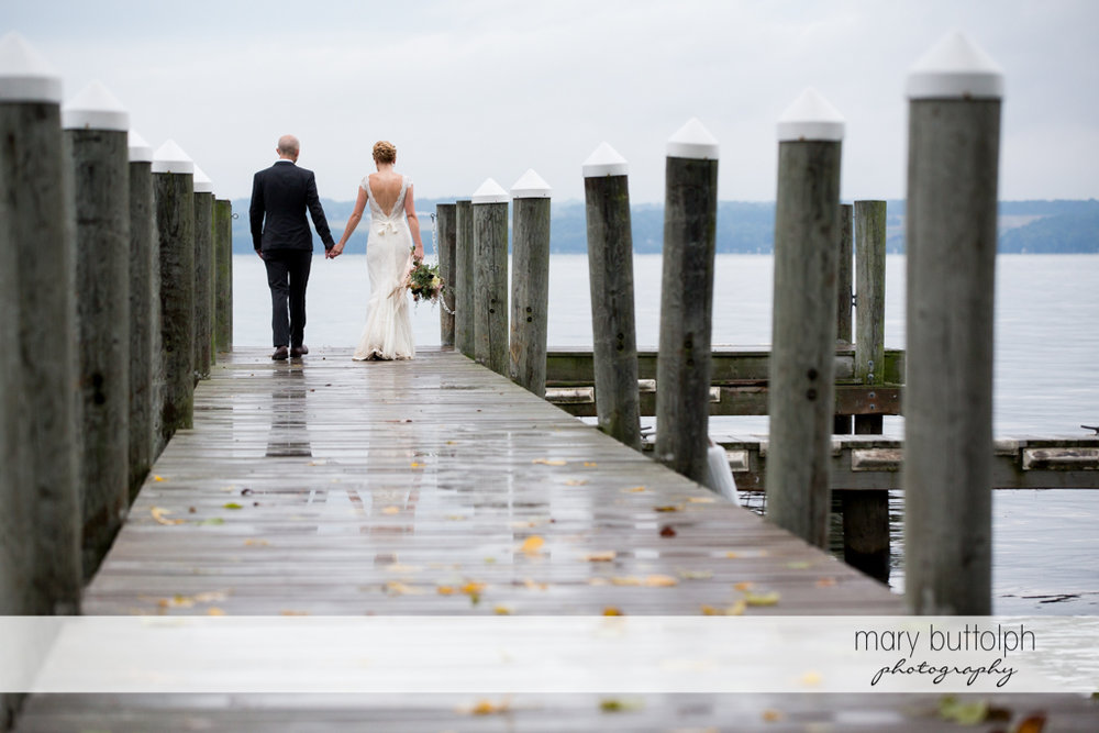 Couple hold hands as they stroll on the dock at the Inns of Aurora Wedding