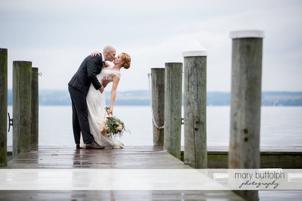 Couple kiss on the dock at the Inns of Aurora Wedding