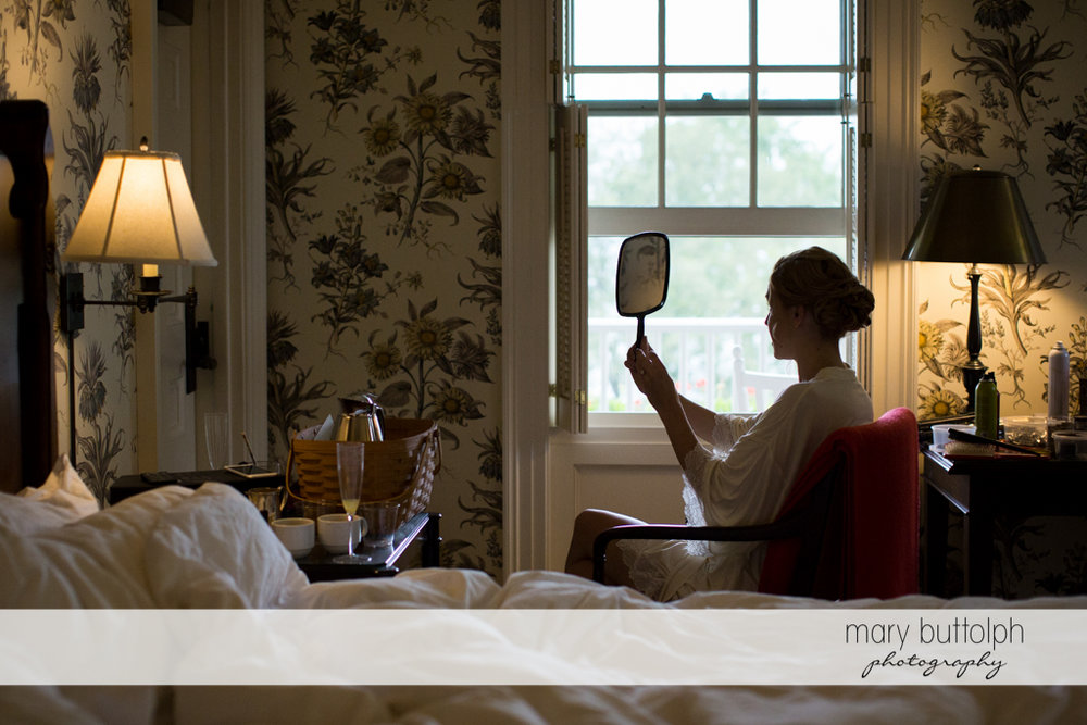 Bride looks at the mirror in her room at the Inns of Aurora Wedding
