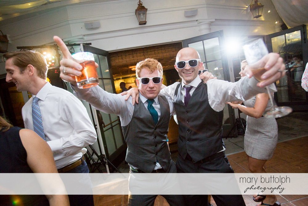 Groom and friend lift their beer glasses at the Inns of Aurora Wedding
