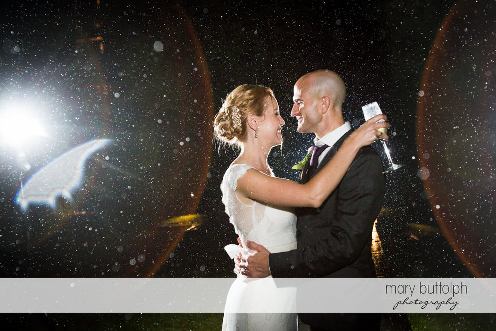 Couple embrace as the rain falls at the Inns of Aurora Wedding
