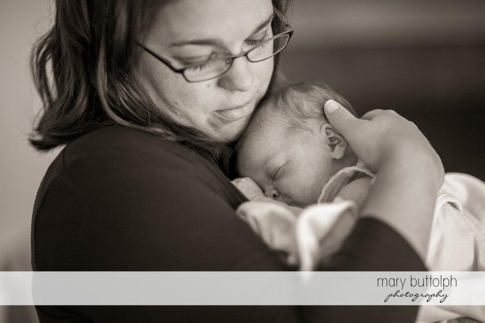Woman puts her baby to sleep at Skaneateles Newborn