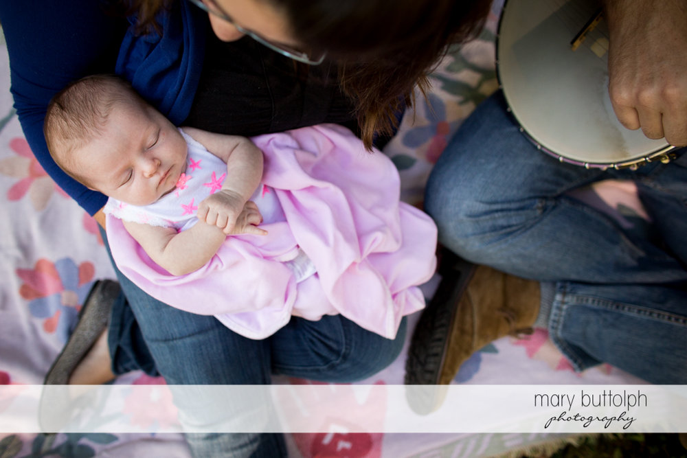 Baby falls asleep while her father plays the banjo at Skaneateles Newborn