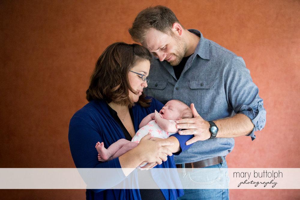 Couple examine their new baby at Skaneateles Newborn