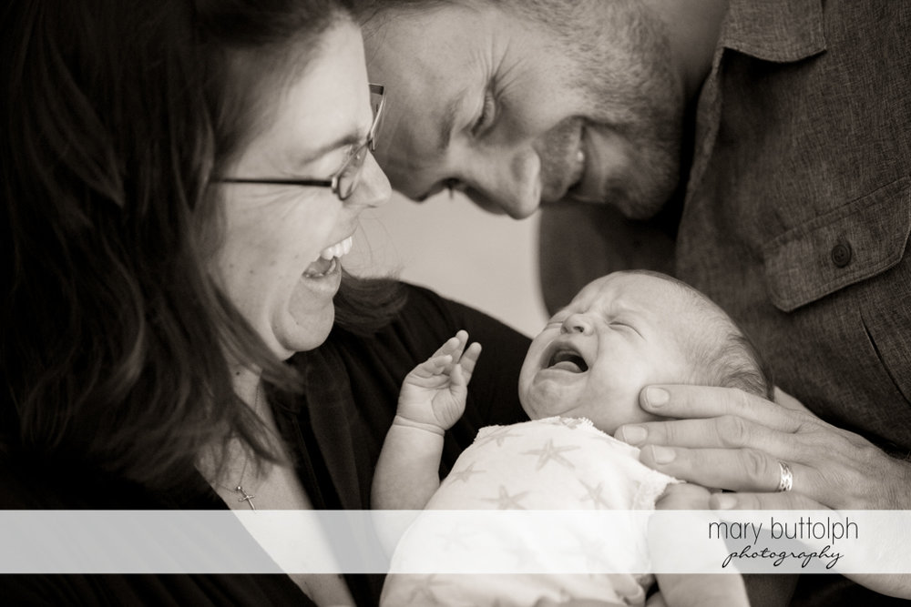 Couple laugh as their new baby cries at Skaneateles Newborn