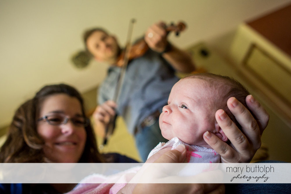 Man plays the violin for his wife and their baby at Skaneateles Newborn