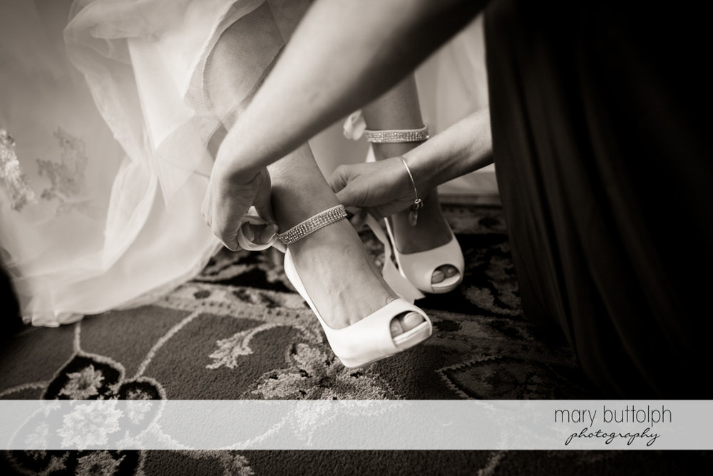 Bride gets help in putting on her shoes at Anyela's Vineyards Wedding
