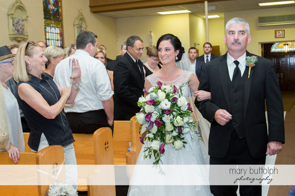Bride and her father walk down the aisle as guests look on at Anyela's Vineyards Wedding