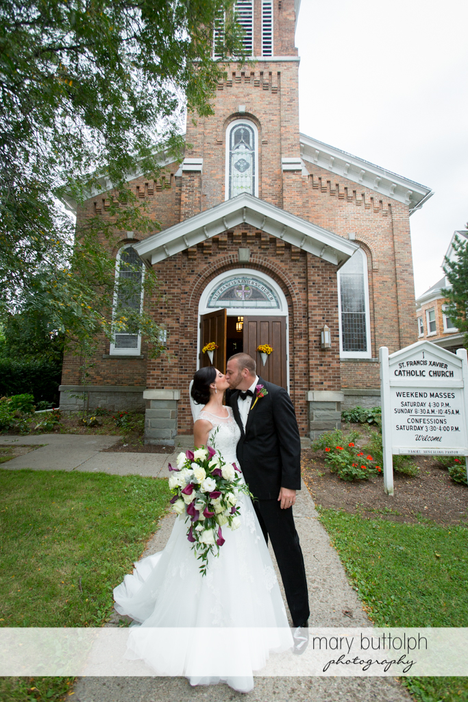 Couple kiss in front of the church at Anyela's Vineyards Wedding