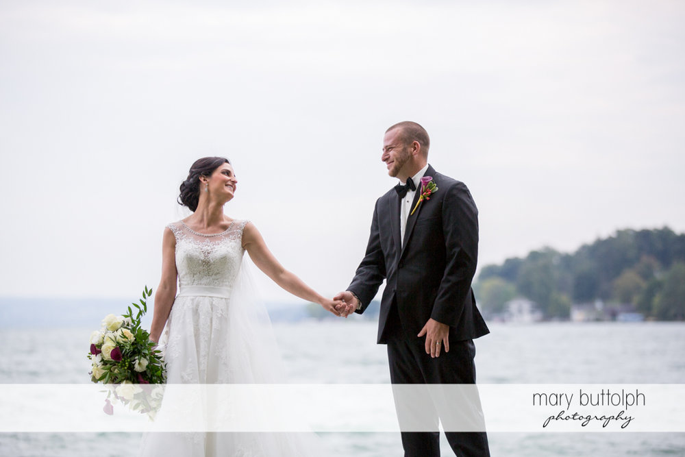 Couple hold hands in front of the lake at Anyela's Vineyards Wedding