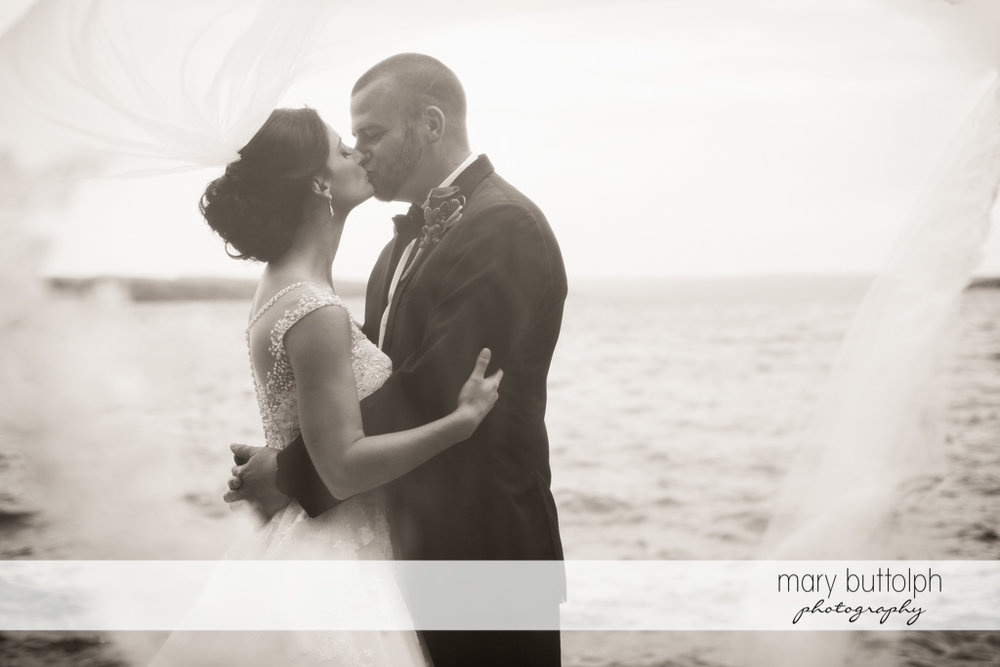 Couple kiss in front of the lake at Anyela's Vineyards Wedding