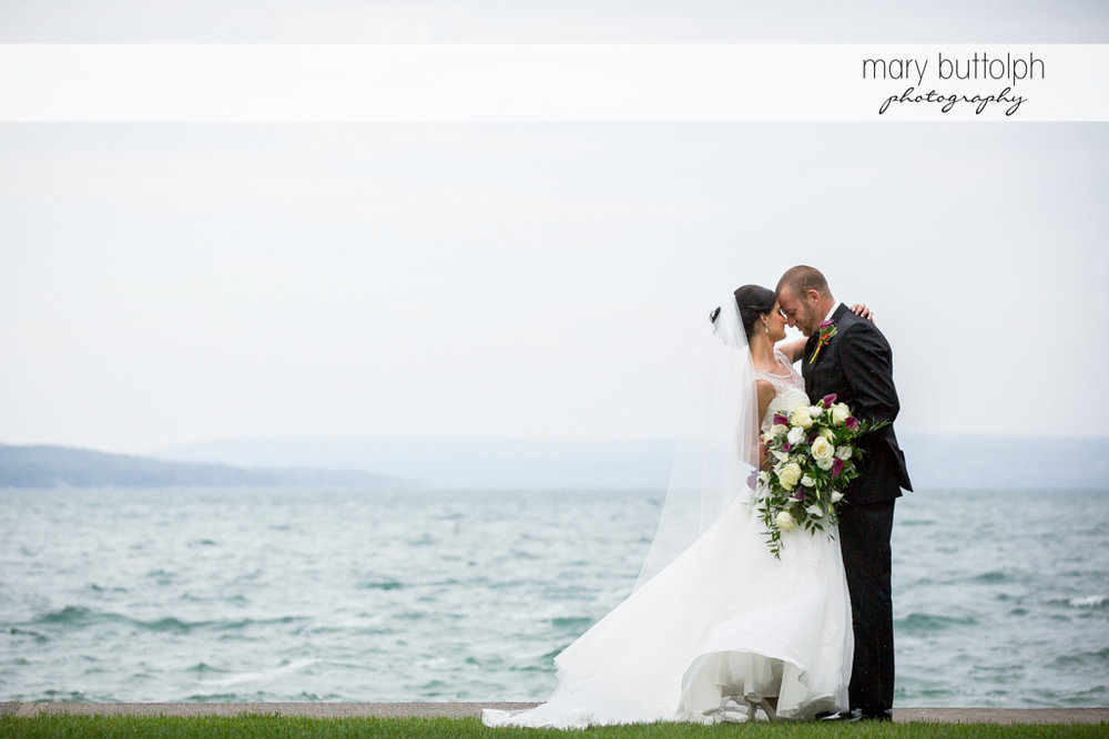 Couple rub noses in front of the lake at Anyela's Vineyards Wedding