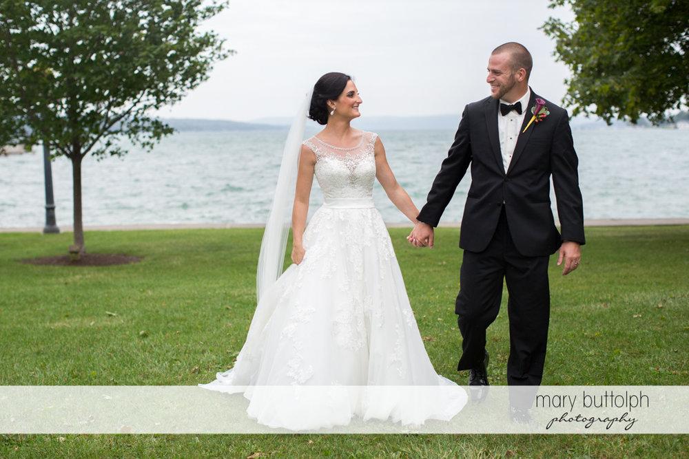 Couple walk hand in hand in the garden near the lake at Anyela's Vineyards Wedding