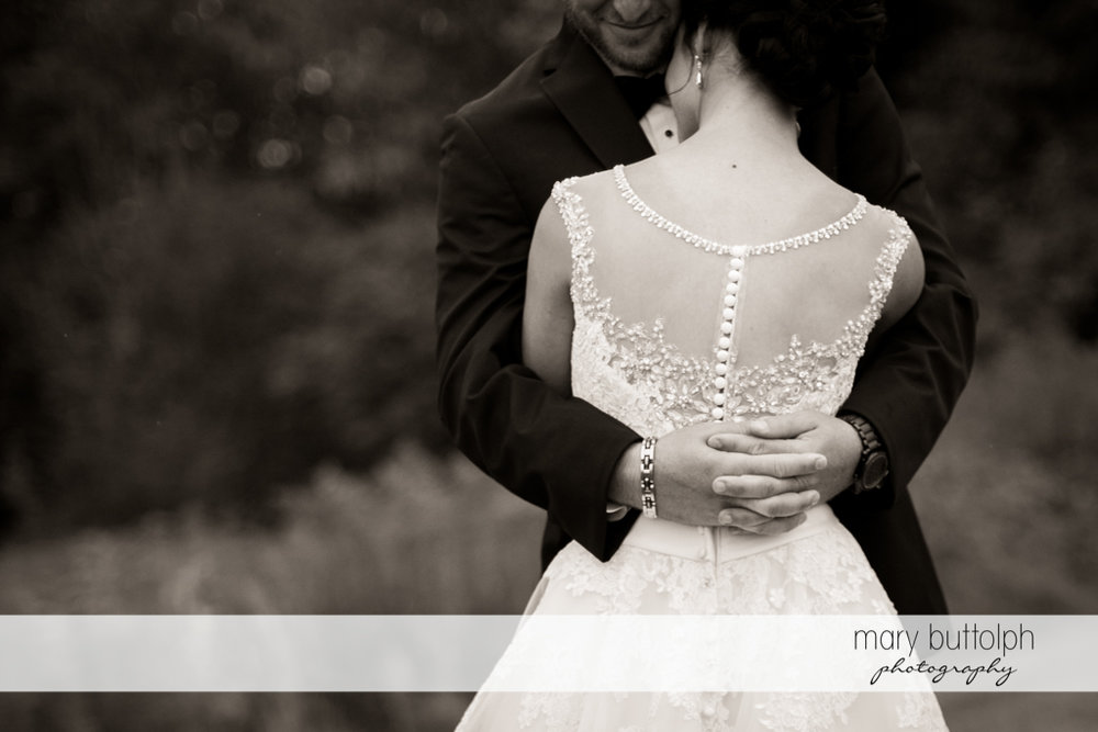 Groom embraces his wife in the garden at Anyela's Vineyards Wedding