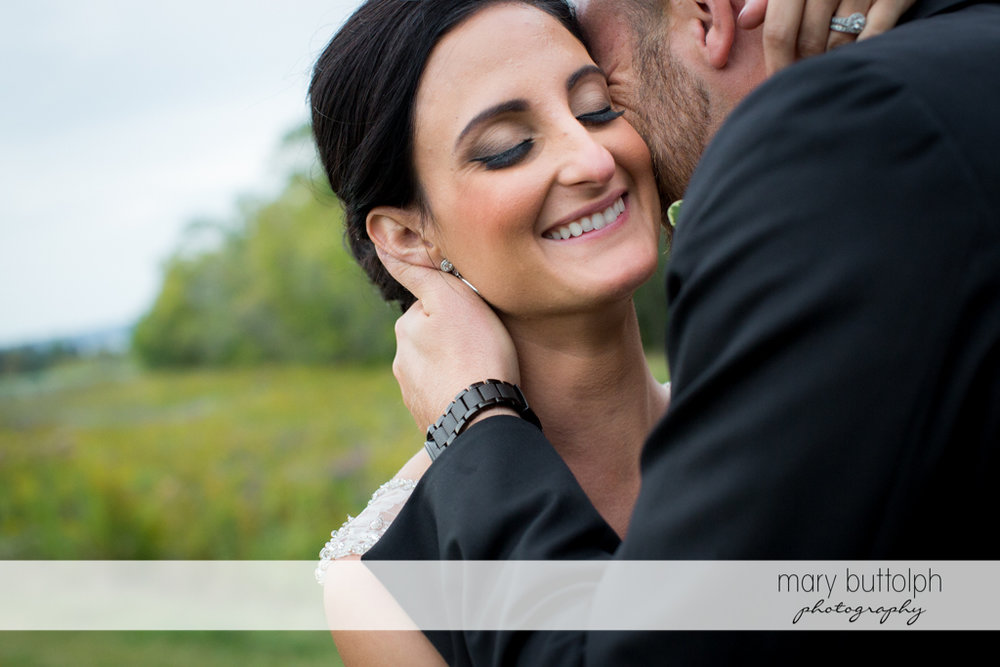 Bride smiles as she is kissed by the groom at Anyela's Vineyards Wedding