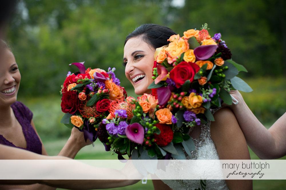 Bridesmaids surround bride's face with flowers at Anyela's Vineyards Wedding