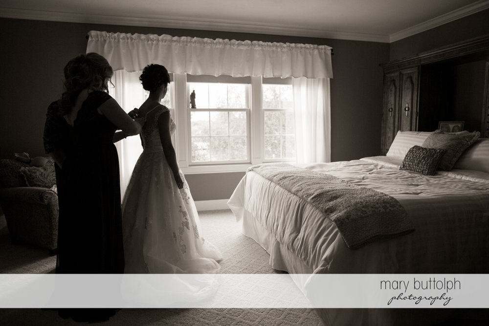 Bride slips on her wedding dress with the help of friends at Anyela's Vineyards Wedding