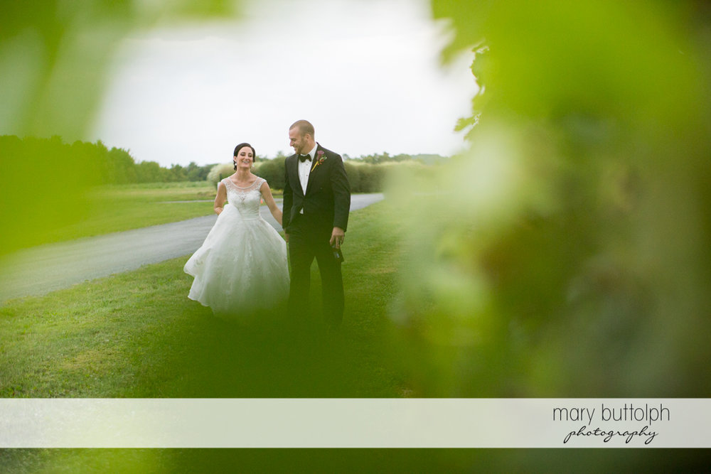 Couple take a quiet stroll in the garden at Anyela's Vineyards Wedding