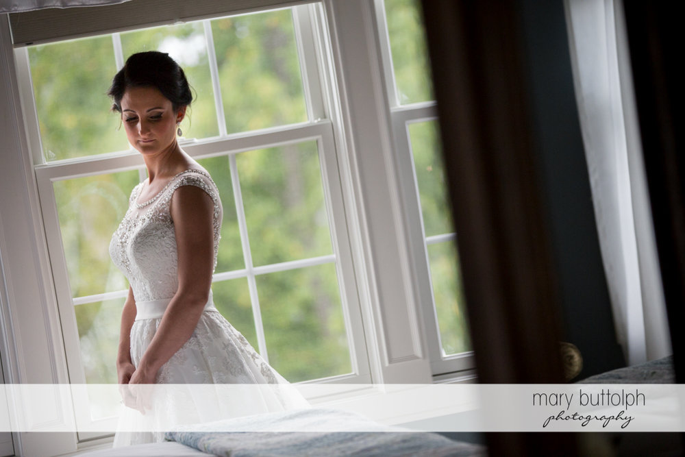 Bride poses in front of the window at Anyela's Vineyards Wedding