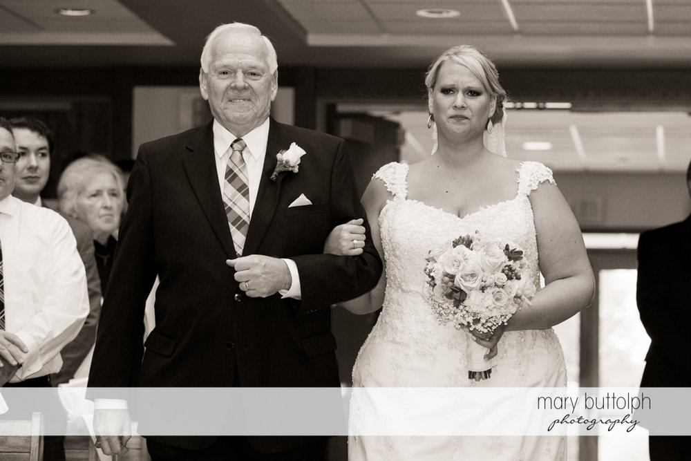 Teary-eyed bride and her father walk down the aisle at the Lodge at Welch Allyn Wedding