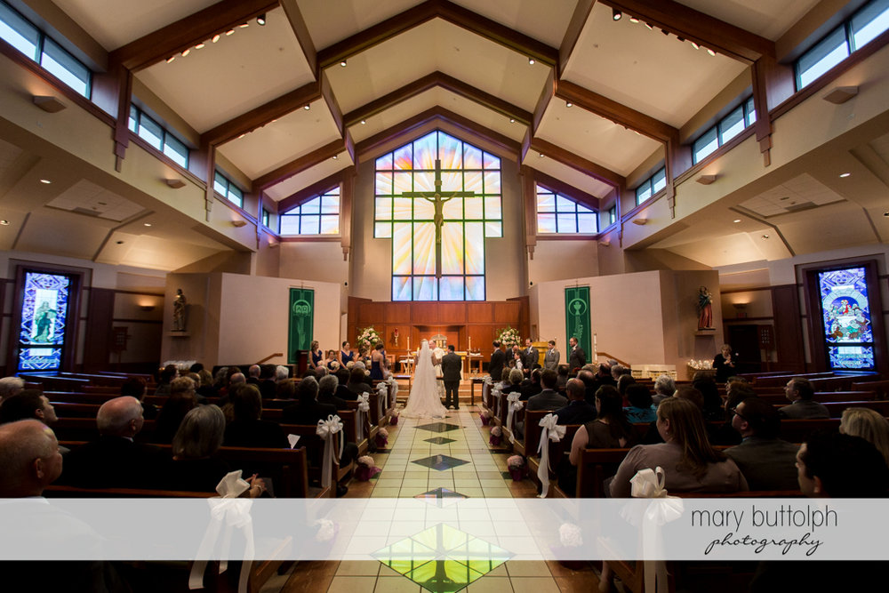 Couple face the altar as guests look on at the Lodge at Welch Allyn Wedding