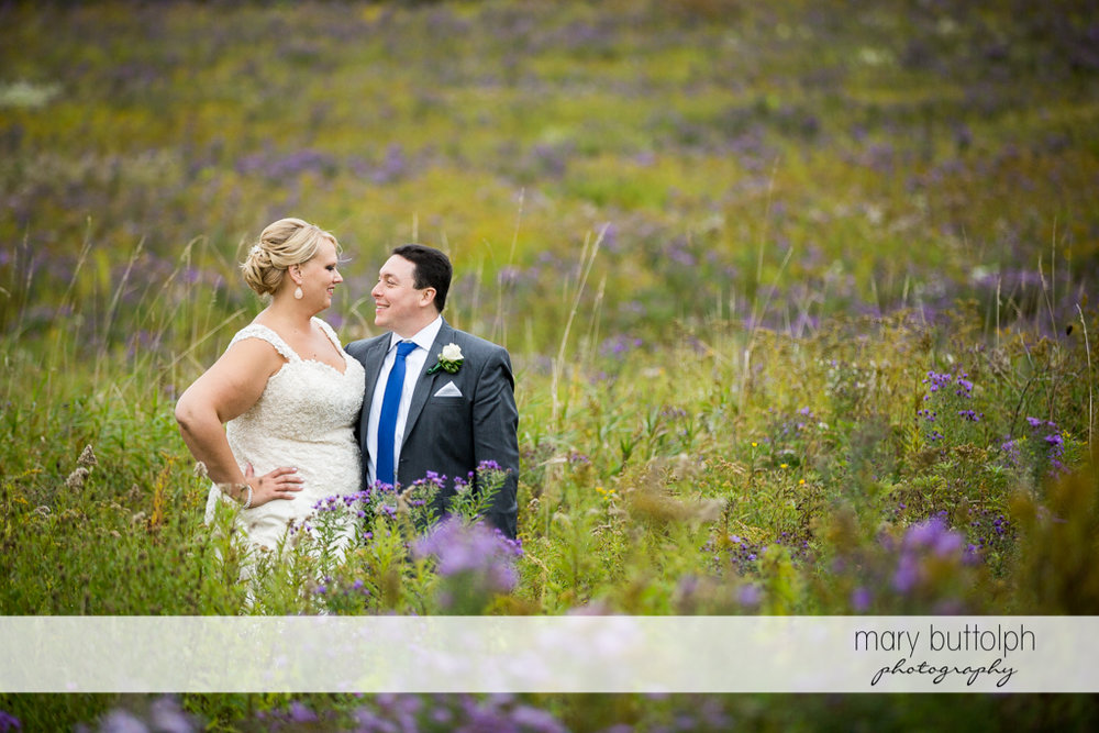 Couple share a happy moment in the meadow at the Lodge at Welch Allyn Wedding