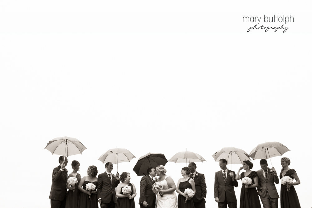 Umbrellas shield the wedding party from the rain at the Lodge at Welch Allyn Wedding
