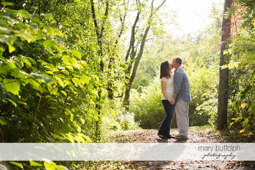 Couple kiss in the park surrounded by trees at Skaneateles Engagement