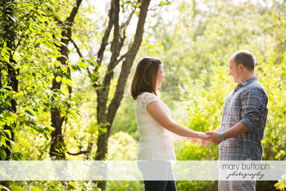 Couple hold hands in the park at Skaneateles Engagement