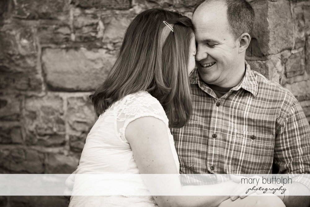 Couple having fun in front of a brick wall at Skaneateles Engagement